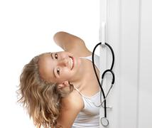 Stock Photo of young woman peeking through door
