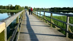 Couple walk hand in hand on wooden bridge through lake Stock Footage