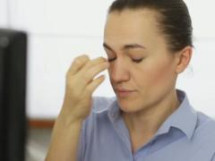Young businesswoman with tired eyes and headache, close up NTSC Stock Footage