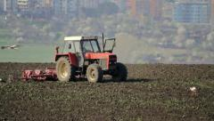 Red tractor plowing a field Stock Footage