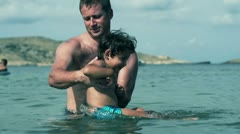Father with his son having fun in the sea, slow motion shot at 120fps Stock Footage