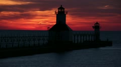 Silhouette of the harbor lighthouse Benton harbor at sunset - Time Lapse Stock Footage