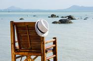 Stock Photo of hat on a bamboo chair on the beach