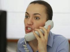 Businesswoman sitting at her desk and screaming into a phone, close up NTSC - stock footage