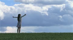 Woman with outstretched hands on a spring field Stock Footage