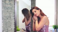 Beautiful woman putting on earrings in bathroom HD - stock footage