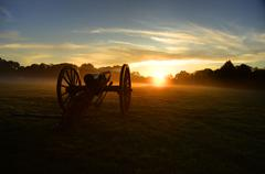 Civil War Cannon at sunrise on misty field - stock photo
