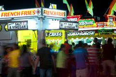 County fair patrons move about fast food vendors Stock Photos