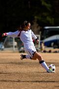 Female Soccer Player Kicks Ball Stock Photos