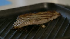Steak comes out of pan close up Stock Footage