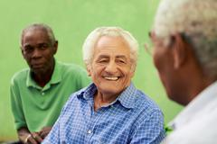 group of old black and caucasian men talking in park - stock photo