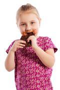 young girl eating a chocolate bar. - stock photo
