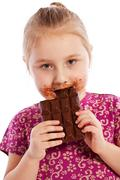 Stock Photo of young girl eating a chocolate bar.