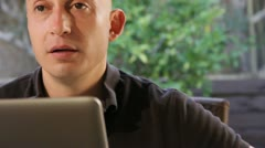Bald man on computer head turn and smile to camera Stock Footage