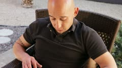 Bald man reading iPad outside Stock Footage