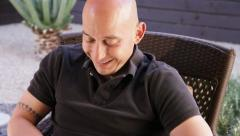 Pan to laughing Bald man texting on iPhone Stock Footage