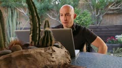 Bald man talking on Skype working at home outside Stock Footage