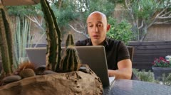 Bald man cracks up on laptop in backyard Stock Footage
