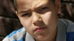 Expressive Hispanic boy CU serious stare to smile Stock Footage
