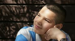 Pensive Hispanic boy with serious look to camera Stock Footage