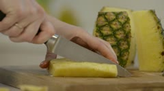 Woman slicing pineapple chunks Stock Footage