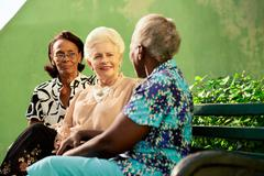 Group of elderly black and caucasian women talking in park Stock Photos