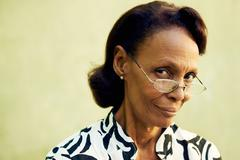 Muotokuva luottavainen vanha musta nainen, jolla on silmälasit hymyilee Kuvituskuvat