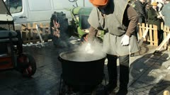 Man jug jar draw hot beer steel pot boil fire spring festival Stock Footage