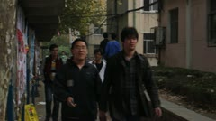 Pan Chinese college students passing by billboard - stock footage