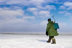 ice fisherman going away - stock photo
