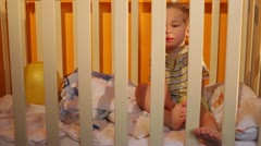 Kid sits in a playpen. Stock Footage
