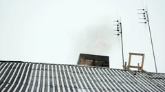 Old house slate roof snow dark smoke rise chimney antenna winter Stock Footage