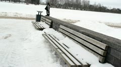 Wooden benches snow woman coat walk winter park Stock Footage