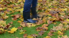 Woman rubber boots walk meadow grass autumn colorful maple leaf Stock Footage