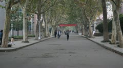 Chinese college students walking on campus street Stock Footage