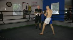 Muay Thai fighter practice his techniques with a coach in a ring Stock Footage