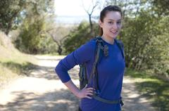 Centered hiker woman in blue long sleeve shirt looks at camera - stock photo
