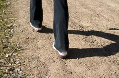 Angled close up of woman's feet hiking in black pants - stock photo