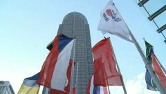 Flags at Messe in Frankfurt with Messeturm skyscraper in the back - stock footage