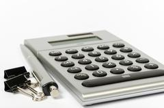 A calculator and a pen on a white background Stock Photos
