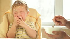 Little boy is crying because he doesn't want to eat more cereal. - stock footage