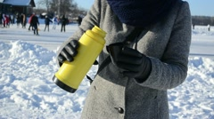 Woman drink hot tea coffee thermos active people skate lake ice Stock Footage