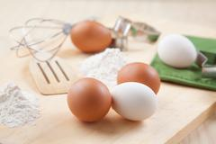 three eggs, flour and whisk on wooden board - stock photo