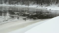 Forest river bay bank cover snow ice floe floating water winter Stock Footage