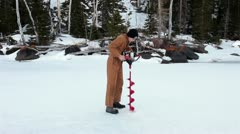 Boy drilling fishing hole in frozen lake winter recreation HD 0881 Stock Footage