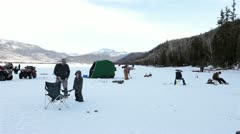 Family scouts ice fishing frozen lake winter recreation HD 0886 Stock Footage