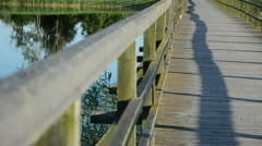Wooden lake bridge railing closeup blur focus change water Stock Footage
