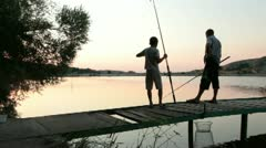 Father and son fishing at dusk Stock Footage