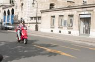 Moped Driver in the Street of Paris Stock Photos