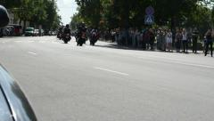 Bikers ride motorcycles in birzai city and people watch Stock Footage